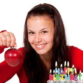 Cartão do aniversário com velas acesas sobre um bolo